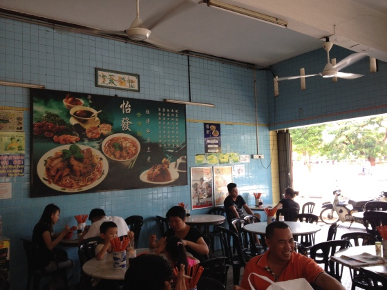 thinning lunch crowd with noodle ads on the wall..