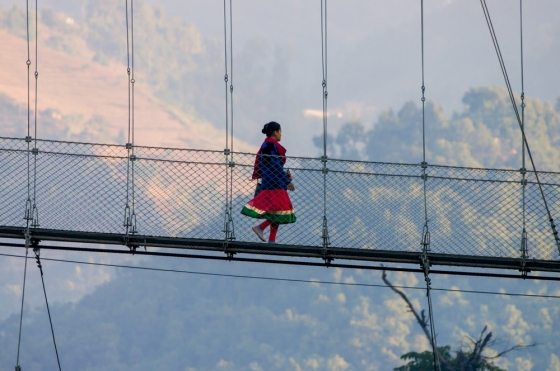 local girl crossing the suspension bridge